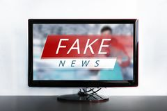 News report with false news. Fake news on the TV screen, HOAX concept. News report with false news. Truth misrepresented in the news on a modern TV. Zombie TV Stock Photos