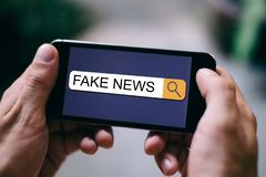 News SEO concept: Close up of Fake News is displayed in Search bar on smartphone display royalty free stock photo