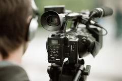 News shooting. Professional camcorder on the tripod, selective focus on nearest part royalty free stock image