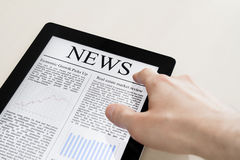 News On Tablet PC. Man hands are touching tablet pc with business news