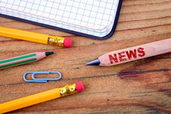 News text on pencil. Social media, propaganda and information. Stationery on an old wooden background royalty free stock images