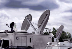 News Truck. Group of satellites news trucks parked together with broadcast dishes aiming toward sky Royalty Free Stock Images