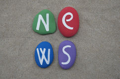 News word on colored stones on the sand Royalty Free Stock Photos
