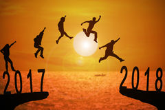2018 News year background. Silhouette group of young mans jumping between 2017 and 2018 years with beautiful sunset at the sea-use for news year and concepts for Stock Images
