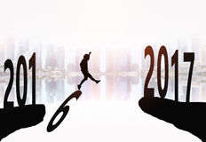 News year 2017 background. Silhouette of young man jumping between 2016 and 2017 years with beautiful city background Vector Illustration