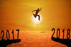 2018 News year background. Silhouette of young man jumping between 2017 and 2018 years with beautiful sunset at the sea Royalty Free Stock Photo