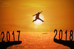 2018 news year background. Silhouette of young man jumping between 2017 and 2018 years with beautiful sunset at the sea-concepts of news year and business target Stock Photos