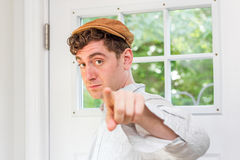 Newsboy Fashion Man. Young handsome curly haired man wearing newsboy hat points finger Stock Image