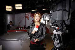 Newscaster with microphone in studio. Attractive television newscaster standing with microphone in front of a video camera in a studio Stock Photography