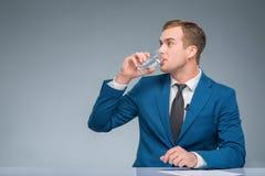 Newsman drinking water at his desk Royalty Free Stock Photos
