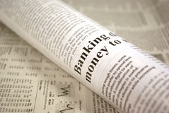 Newspaper. Rolled-up newspaper on background of financial newspaper concept Stock Photo