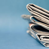 Newspaper. A stack of newspaper on blue background Royalty Free Stock Image