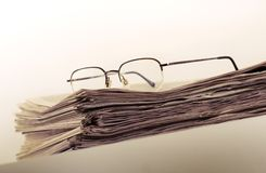 Newspaper. Pile of newspaper with eyeglasses stock images