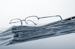 Newspaper. Pile of newspaper with eyeglasses royalty free stock photo