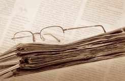 Newspaper. Pile of newspaper with eyeglasses royalty free stock image