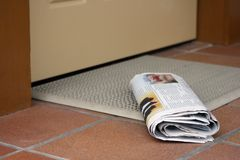 Daily newspaper. Waiting to be picked up outside home entrance door Stock Image