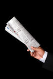Newspaper. In businessman hand on black background Royalty Free Stock Photo