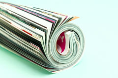 Newspaper. Newsprint rolled up, on green background Royalty Free Stock Images