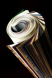 Newspaper. Rolled up black background isolate Royalty Free Stock Image