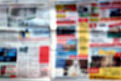 Bright newspaper photographed blurry stock image