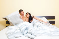 Newspaper bed couple Royalty Free Stock Photos