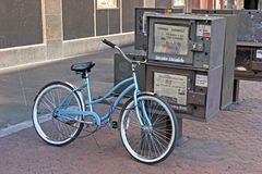 Newspaper & Bike. Bike leaning against nwspaper rack royalty free stock photos