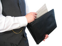 Newspaper in Briefcase. A Man in a business suit pulls a newspaper out of his black briefcase Royalty Free Stock Photos
