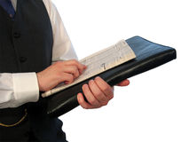 Newspaper on Briefcase. A man in a business suit holding a newspaper and a black briefcase royalty free stock image