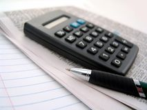 Newspaper, calculator and pen Royalty Free Stock Photography
