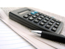 Newspaper, calculator and pen Royalty Free Stock Photo