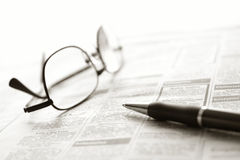 Newspaper Classified Ads with Glasses and Pen. Ballpoint pen and reading glasses on newspaper jobs and help wanted employment classifieds ads section for an stock photography