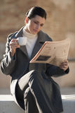 Newspaper and coffee. Young businesswoman taking a rest with newspaper and coffee Royalty Free Stock Photos