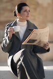 Newspaper and coffee. Young businesswoman taking a rest with newspaper and coffee Stock Images