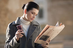 Newspaper and coffee. Young businesswoman taking a rest with newspaper and coffee Royalty Free Stock Image