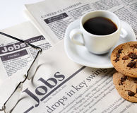 Newspaper and coffee. Newspaper classifieds and coffee cup with cookies Royalty Free Stock Images