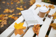 Newspaper and coffee cup on bench in autumn park Stock Images