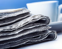 Newspaper and coffee cup.Blue background Royalty Free Stock Images