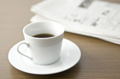 A newspaper and coffee on the desk Stock Photo