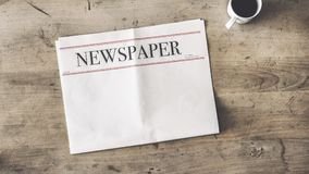 Newspaper and coffee on wooden background stock photo
