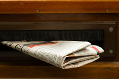 Newspaper coming in the mail box stock photos