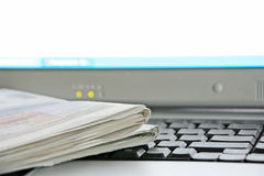 Newspaper and Computer. A newspaper on the keyboard of a laptop computer (focus is on the corner of the newspaper Royalty Free Stock Images