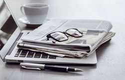 Newspaper with computer on table Royalty Free Stock Images