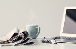 Newspaper with computer on table Royalty Free Stock Photography