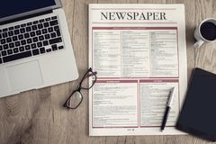 Newspaper with computer on wooden background stock photography