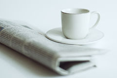 Newspaper and a cup of coffee. On a white background royalty free stock images