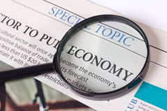 Newspaper economic article. With lying on it magnifying glass stock images