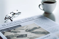 Newspaper with eyeglasses on white table Stock Image