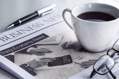 Newspaper with eyeglasses on white table Stock Photography
