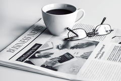 Newspaper with eyeglasses on white table Royalty Free Stock Photos