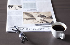 Newspaper with eyeglasses on wooden table Stock Photos